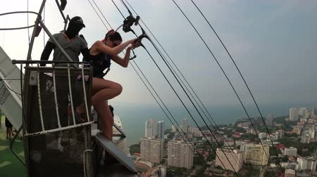 zipline : Extreme Jump from the Pattaya City Tower. Woman goes down the cable from the roof Stock Footage