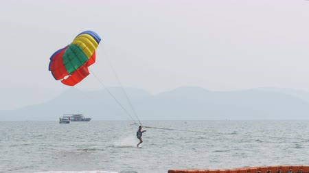 propulsion : Parasailing, a man is flying on a parachute for a boat. Pattaya, Thailand