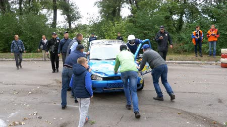 excesso de velocidade : The spectators help to turn over the rally car on the roof. Accident with Rally car