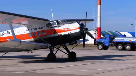 Small Airplane with Propeller Standing on the Aircraft Parking near the Hangar on a Small Airfield Stock Footage