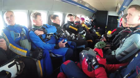 svetr : Group of parachutists sits inside a small plane awaiting a jump