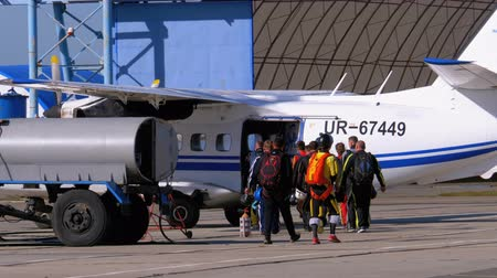 Group of skydivers goes to the plane parked near the hangar on a small airfield