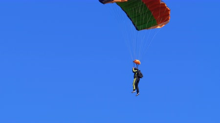 Skydiver flying with a parachute and landed on the ground Stock Footage