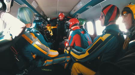 Group of skydivers sits inside a small plane awaiting a jump. Slow Motion Stock mozgókép