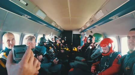 Group of skydivers sits inside a small plane awaiting a jump