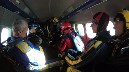 Group of parachutists sits inside a small plane awaiting a jump. Slow Motion