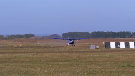 Small airplane with a rotating propeller is moving along a runway with a ground coating