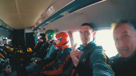 Group of parachutists sits inside a small plane awaiting a jump