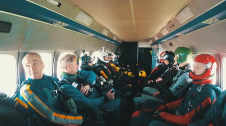 aircraft cabin : Group of skydivers sits inside a small plane awaiting a jump. Slow Motion Stock Footage
