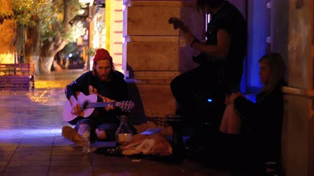 Street musicians in the city play the guitars at night