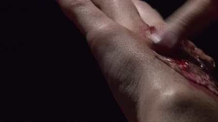 frightful : Soft focus close up shoot making halloween make up fake scar on girl wrist hand, dark background