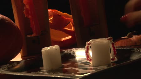 sharpened : Hand take lighter and light candles on Halloween table with pumpkins and vampire bloody teeth