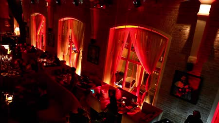 moscow night : RUSSIA, MOSCOW, 31.10.2015: Restaurant interior Halloween party, People relaxing and drinking in night club, scary dark interior in red light, high angle, long shot Stock Footage