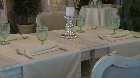 beautifully : Beautifully served table with white tablecloth and chairs, glasses for wine and silver cutlery and white fabric napkins Stock Footage