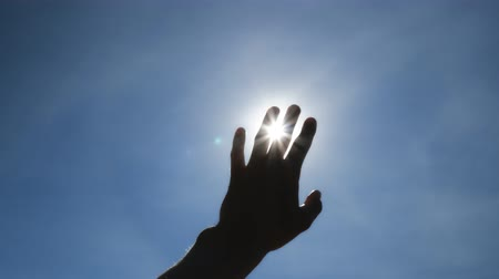 god ray : Hand of man, strive for sun and deep blue sky. Conceptual scene.