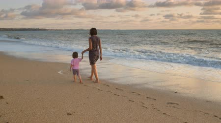 Mother and daughter walking at the sunset time. Concept of happy friendly family.