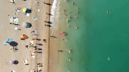 Aerial view of the beach filled with hot sunny day. People rest near the sea ocean. Stock Footage