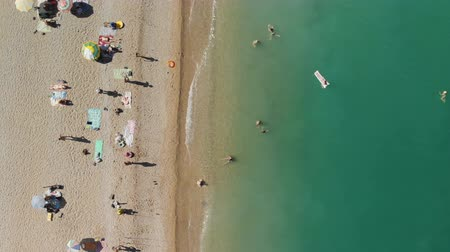 üst : Aerial view of the beach filled with hot sunny day. People rest near the sea ocean. Stok Video