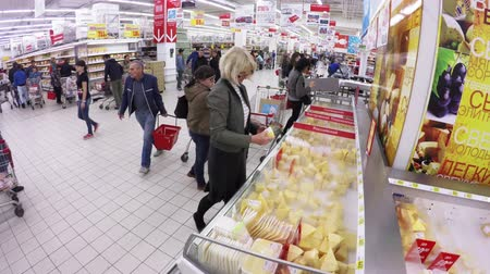 nagylátószögű : MOSCOW  SEPTEMBER 29, 2015:  Blonde chooses cheese in the hypermarket Stock mozgókép