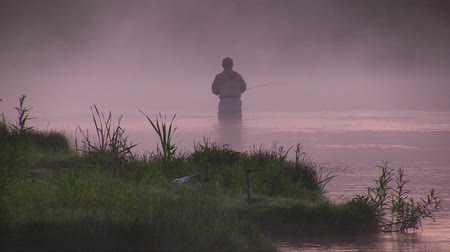 каноэ : angler catches fish at dawn in the fog