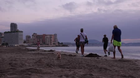 group of people walking along the beach in Calpe, Spain