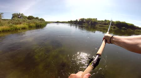 The fisherman throws a fly fishing tackle with a two-handed fly fishing rod.