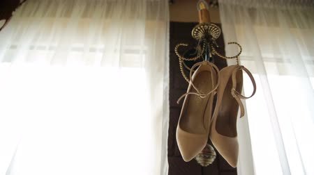 high heeled sandals : Wedding shoes hang on the sconces