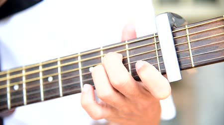 Musician playing finger style on acoustic guitar with capo