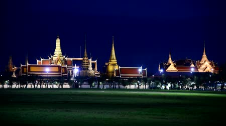 kaew : Bangkok , Thailand - 20 June, 2019 :  wat phra kaew with green grass field and lighting in night time