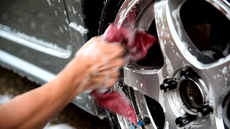 the man wash the wheel of car