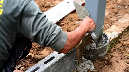 кирпичная кладка : Worker brick the cement wall in construction site