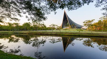 príncipe : Nakhon Pathom, Thailand - 18 Dec, 2019 : Zoom in time lapse Prince Mahidol Hall building of Mahidol university with reflections of the sun on the lake view