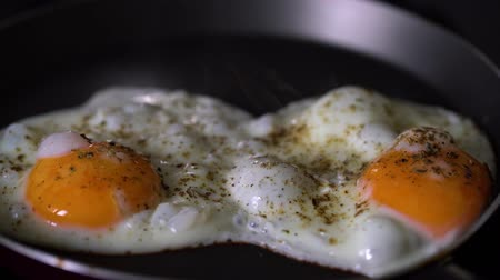 Fry eggs in a frying pan. Breakfast. Seasoning. Steam. Stock mozgókép