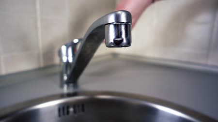 Woman opens water tap. Tap water flows from the kitchen in slow motion. City life modern human. Videography of home life.