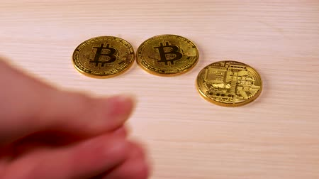Man puts golden bitcoins btc bit coin on table. Wealth. Economy. Cryptocurrency in cyberspase. Mining Hand.