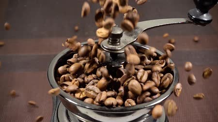 americano : Coffee beans fall into the coffee grinder. Slow motion video. Preparation of morning coffee for breakfast. Mill for grinding. Stock Footage