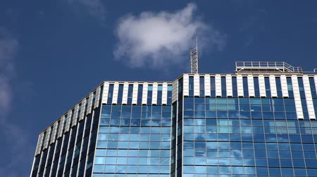 puffy clouds : Puffy white clouds with a fast motion effect moving through a city sky reflecting off of a glass building. Stock Footage