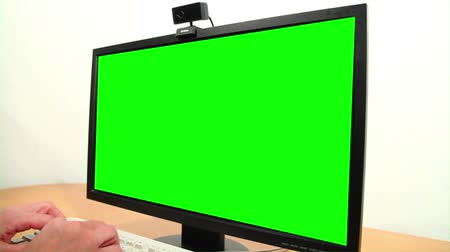 Close-up of mans hands typing on a keyboard and a green screen.
