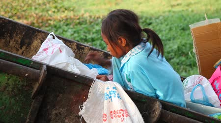 csavargó : Little girl looking in garbage bins themselves anything should eat. The harsh reality of modern life. Cambodia.
