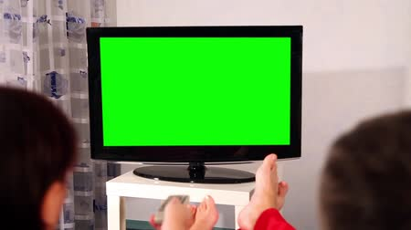 tv screen : Man and woman watching television. Green screen.