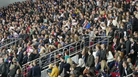 torcendo : Fans at sporting events closely watching the game of hockey.