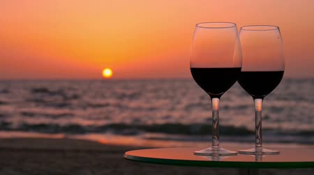 şarap cam : On the glass table with two glasses of red wine. The table is located on the beach. Sunset. Tracking. Stok Video