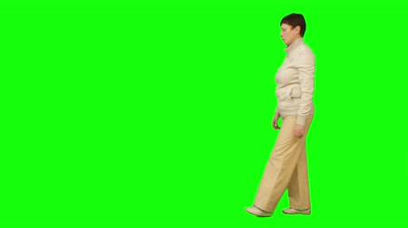 isolar : Woman goes from right to left. Green screen.