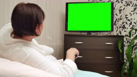 assistindo : Woman watching TV with green screen. Dolly shot.
