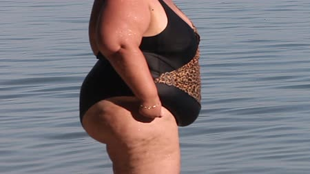 диета : Women with overweight standing in a swimsuit at the water surface.