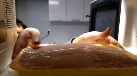 Woman puts the meat in the microwave to defrost. Stock Footage