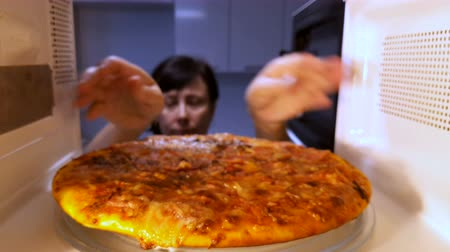 Woman puts pizza in the microwave.