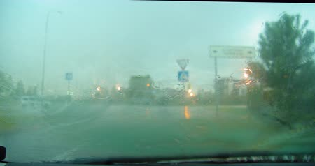 Heavy rain from inside car with windscreen wiper going.
