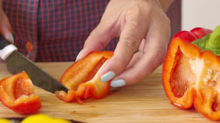 Close up cook cuts sweet pepper on a cutting board.