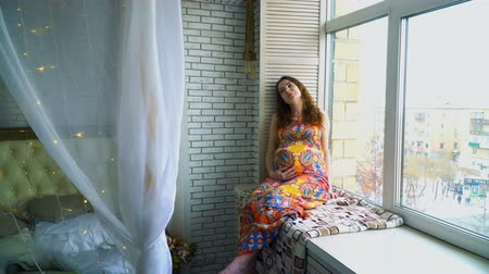 brilho : Young beautiful pregnant girl sits near a window
